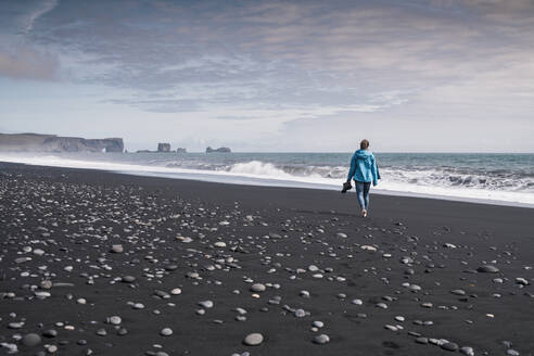 Young woman walking on barefoot on a lava beach in Iceland - UUF18666