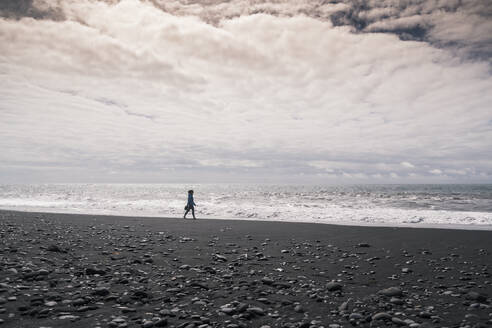 Young woman walking on barefoot on a lava beach in Iceland - UUF18669