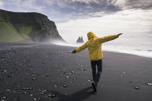 Mature man walking on a lava beach in Iceland, with arms outstretched - UUF18675