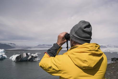 Mature man watching Vatnajokull glacier with binoculars, Iceland - UUF18708