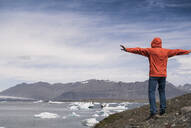 Mature man looking at  Vatnajokull glacier, Iceland, with arms out stretched - UUF18717
