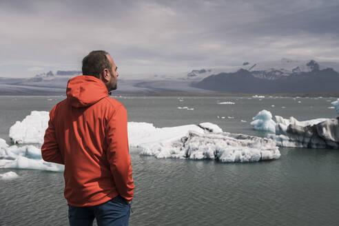 Mature man watching Vatnajokull glacier, Iceland - UUF18720