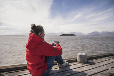 Young woman sitting on a jetty, drinking coffee, South East Iceland - UUF18732