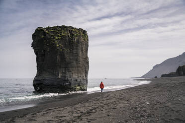 Woman on lava beach in South East Iceland, walkng at the sea - UUF18738