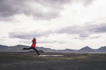 Mature man jumping for joy in the Highland Region, Iceland - UUF18750