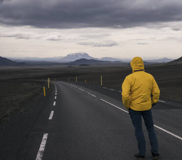 Man standing at  empty road, looking at distance, Iceland - UUF18753