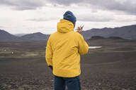 Mature man talking on his smartphone in the Icelandic highlands - UUF18759