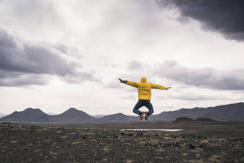 Mature man jumping for joy on a lava beach in Iceland - UUF18765