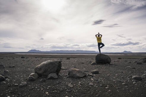 Mature man balancing on one leg on a rock in the volcanic highlands of Iceland - UUF18771