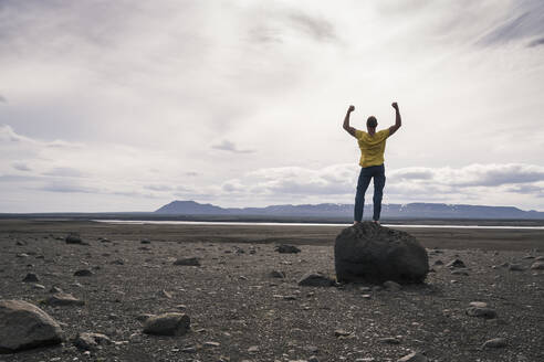 Mature man standing on a rock in the volcanic highlands of Iceland with raised arms - UUF18777