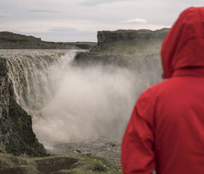 Young woman looking at Dettifoss waterfalls, Iceland - UUF18783