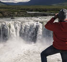 Man looking at Godafoss waterfalls, Iceland, with binoculars - UUF18795