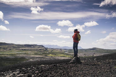 Hiker in Vesturland, Iceland, standing and looking at landscape - UUF18813