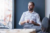 Businessman in office having a coffee break - DIGF07911