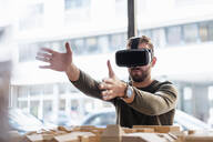 Man with architectural model in office wearing VR glasses - DIGF07914