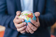 Close-up of businessman holding miniature globe in office - DIGF07935