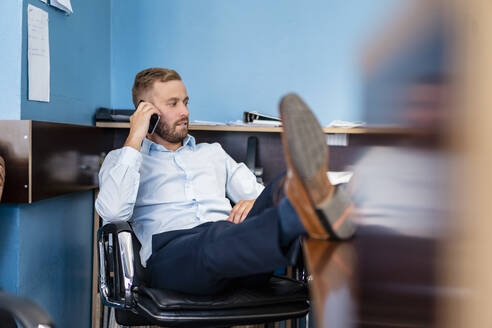 Businessman on cell phone in office - DIGF07950