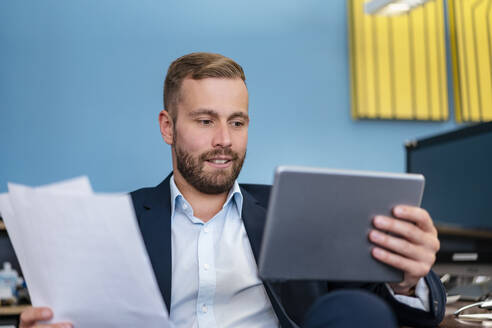 Businessman with papers and tablet at desk in office - DIGF07956