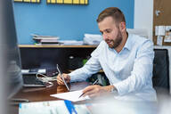 Businessman with papers and tablet at desk in office - DIGF07959
