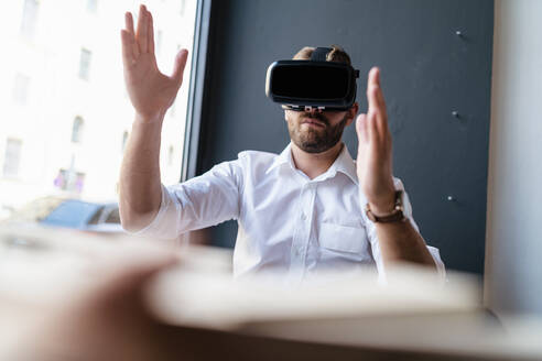 Businessman with architectural model in office wearing VR glasses - DIGF07977