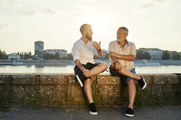 Father and adult son sitting on a wall at the riverside talking - ZEDF02534