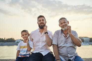 Portrait of smiling father and adult son with gandson scratching their beards - ZEDF02552