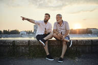 Father and adult son sitting on a wall at the riverside at sunset drinking a beer - ZEDF02555