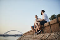 Father and adult son sitting on a wall at the riverside talking - ZEDF02558