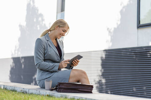 Smiling blond businesswoman sitting on a wall outdoors using digital tablet - DIGF08014