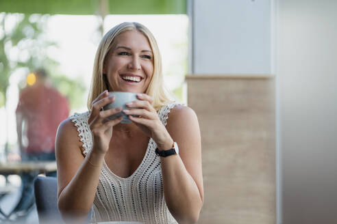 Portrait of happy blond woman drinking coffee in a cafe - DIGF08020
