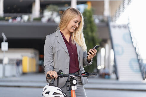 Smiling businesswoman with electric scooter looking at cell phone - DIGF08026