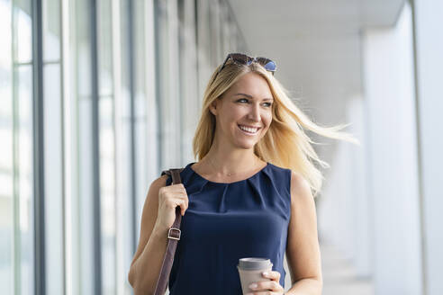 Portrait of smiling blond businesswoman with coffee to go in summer - DIGF08044