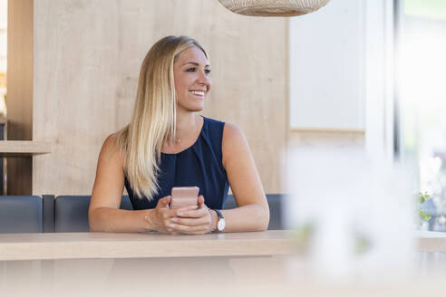 Portrait of smiling blond businesswoman with smartphone waiting in a coffee shop - DIGF08050