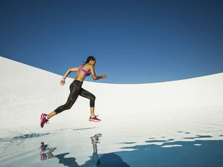 Mixed race woman running on water surface - BLEF14281