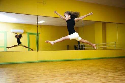 Mixed race girl leaping in ballet studio - BLEF14296