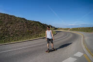 Young man longboarding on empty country road - AFVF03792