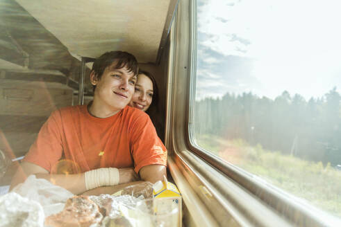 Caucasian couple looking out train window - BLEF14359