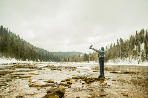 Caucasian hiker with arms outstretched standing in remote river - BLEF14458