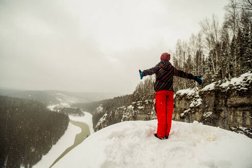 Caucasian hiker standing with arms outstretched on snowy hilltop - BLEF14464