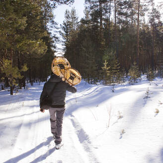 Mari man carrying snowshoes on snowy path - BLEF14533