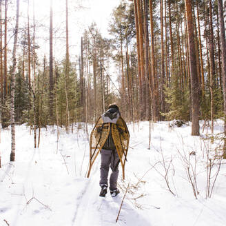 Mari man carrying snowshoes in snowy forest - BLEF14536