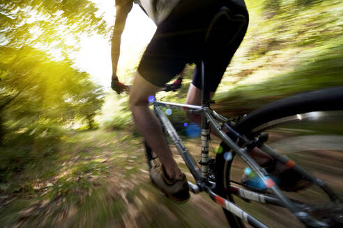Blurred view of Caucasian man riding dirt bike in forest - BLEF14539