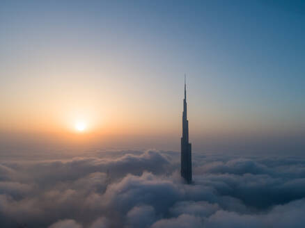 Aerial view of Burj Khalifa Tower in a sea of clouds at sunset in Dubai, United Arab Emirates. - AAEF01753
