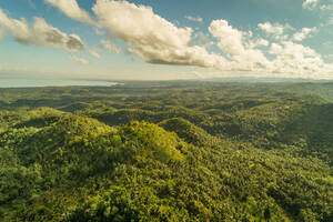 Aerial view of lush green hills by Tanon Strait, Philippines. - AAEF01774