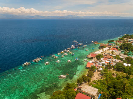 Aerial view of resort, coral reef and filipino boats, Moalboal, Philippines. - AAEF01813