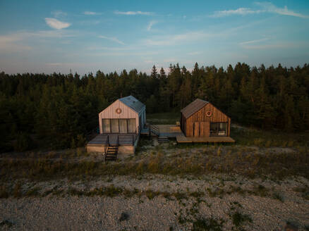 Aerial view of two houses on the beach at sunset - AAEF02003