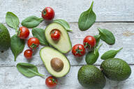 Directly above shot of avocados with tomatoes and spinach on wooden table - ASF06491