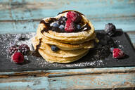 Close-up of pancakes with chocolate sauce and various berries on table - MAEF12926