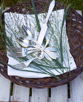 Silverware and leaves in wicker basket on wooden table n backyard party - PPXF00221