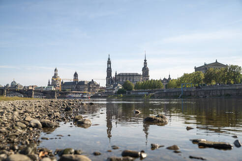 Elbe river by Hofkirche und Semperoper against sky in city during sunny day, Saxony, Germany - CHPF00566